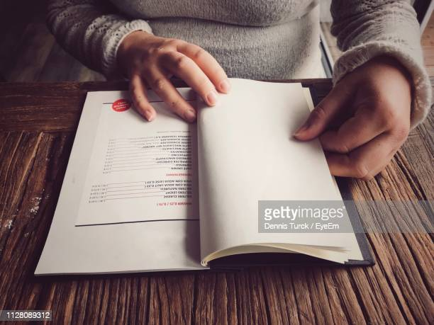 midsection of woman reading menu on table - menu stock pictures, royalty-free photos & images