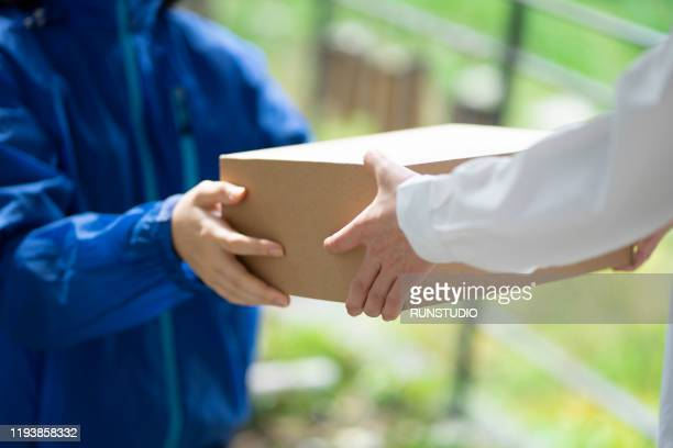 midsection of woman receiving package from delivery person - 受ける ストックフォトと画像