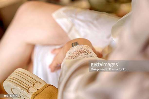 midsection of woman relaxing on chair at home - human leg stock pictures, royalty-free photos & images