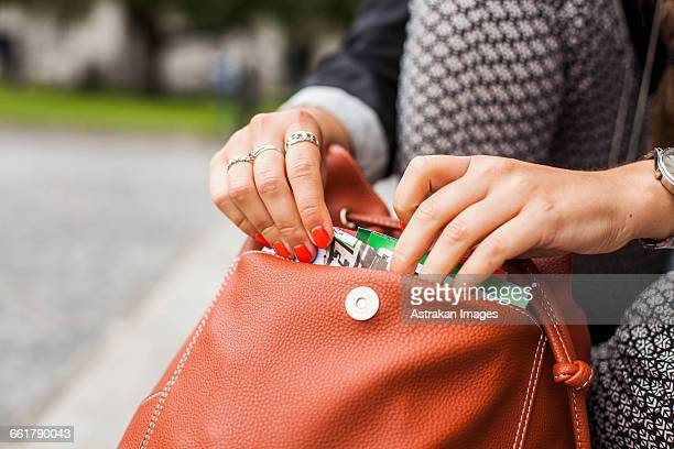Midsection of woman removing book from bag outdoors