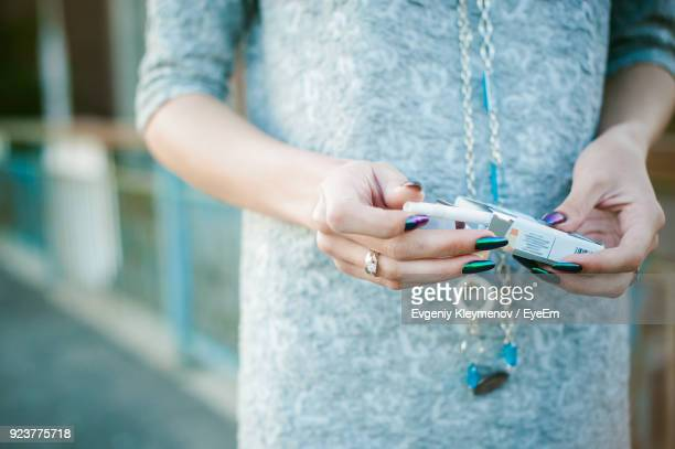 midsection of woman removing cigarette from packet - cigarette pack stock pictures, royalty-free photos & images