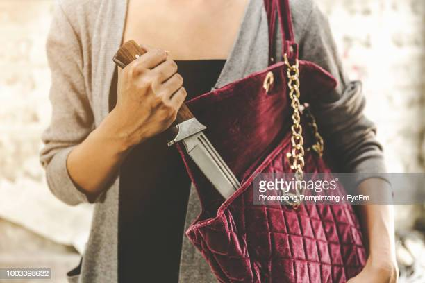 Midsection Of Woman Removing Knife From Purse