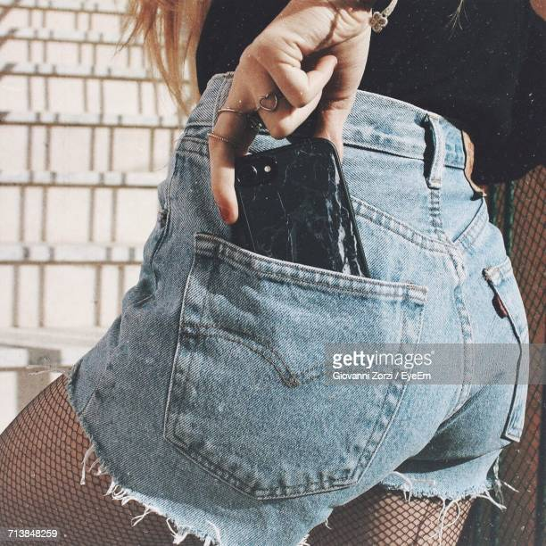midsection of woman removing mobile phone from back pocket - pocket stock photos and pictures