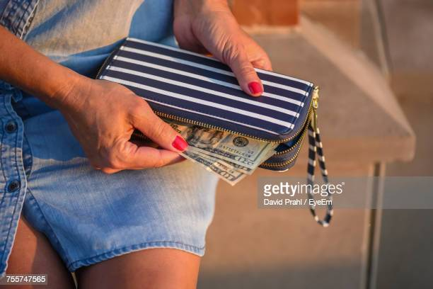 Midsection Of Woman Removing Paper Currency From Purse