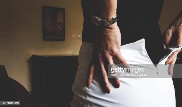 midsection of woman removing white skirt at home - femme se deshabille photos et images de collection