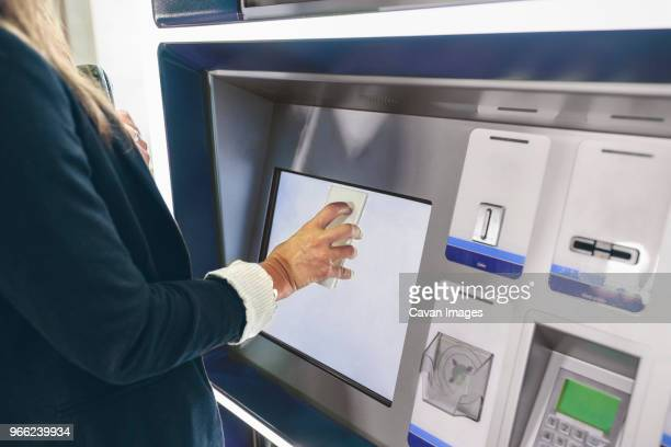 midsection of woman scanning mobile phone while buying train ticket - security check fotografías e imágenes de stock