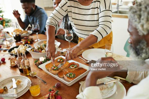 midsection of woman serving appetizers to friends - vegetarianism stock pictures, royalty-free photos & images
