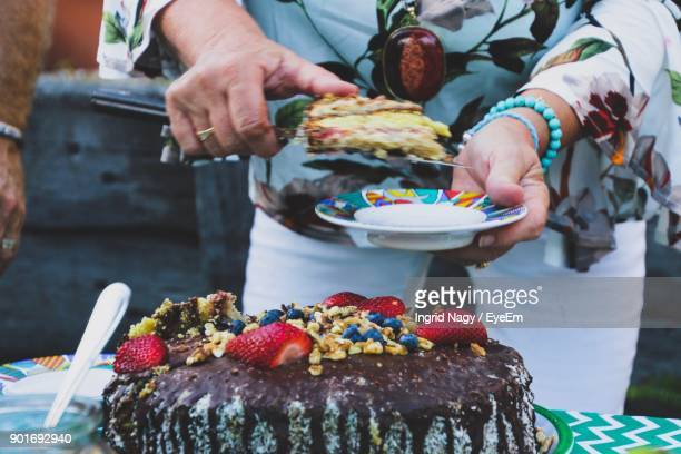 Midsection Of Woman Serving Cake In Plate
