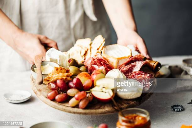 midsection of woman serving meze platter on table - antipasto stock pictures, royalty-free photos & images