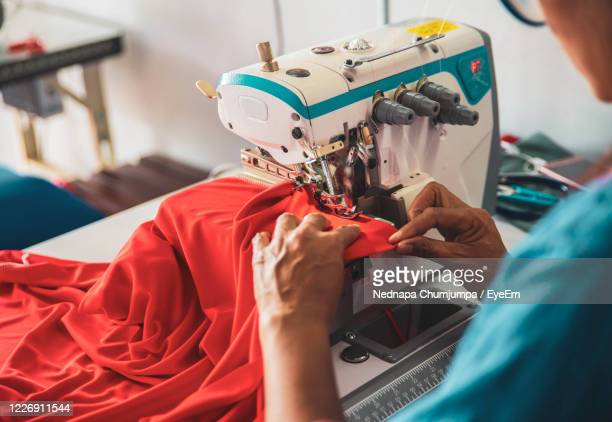 midsection of woman sewing cloth - garment stock pictures, royalty-free photos & images