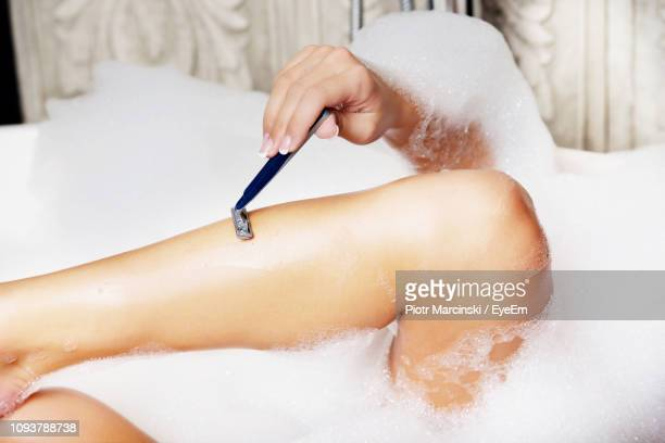midsection of woman shaving leg in bathtub - razor stock pictures, royalty-free photos & images