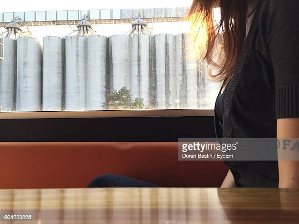 Midsection Of Woman Sitting By Window