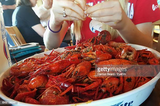 Midsection Of Woman Sitting In Front Of Cooked Crawfish At Restaurant