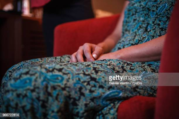 midsection of woman sitting on chair - mid section stock photos and pictures