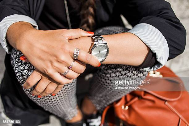 midsection of woman sitting on steps outdoors - wrist watch stock pictures, royalty-free photos & images