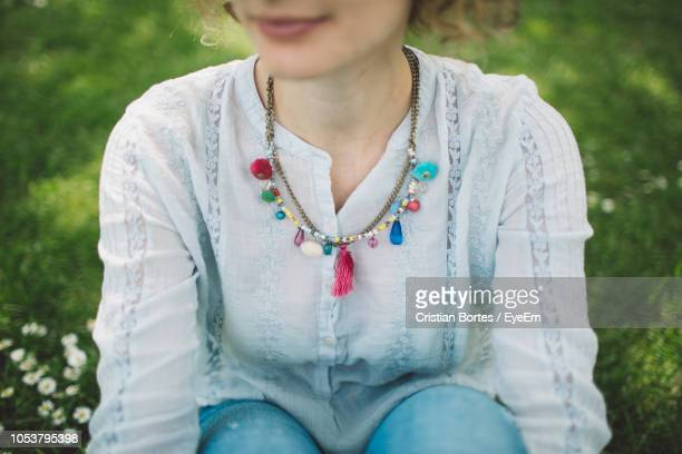 Midsection Of Woman Sitting Outdoors