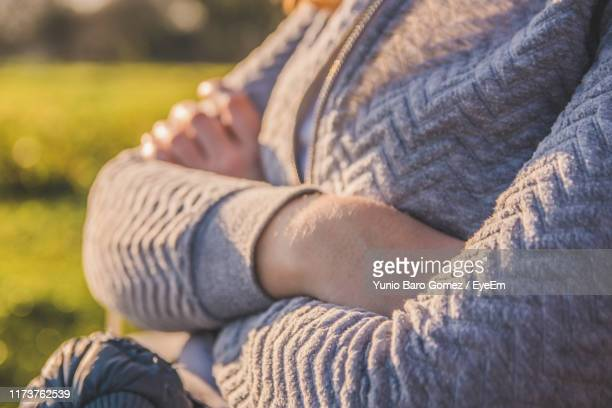 midsection of woman sitting outdoors - mid section stock pictures, royalty-free photos & images