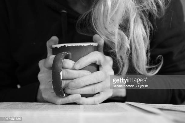 midsection of woman sitting while holding coffee cup - sabine kriesch stock-fotos und bilder