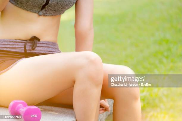 midsection of woman sitting with dumbbell at park - 膝 ストックフォトと画像