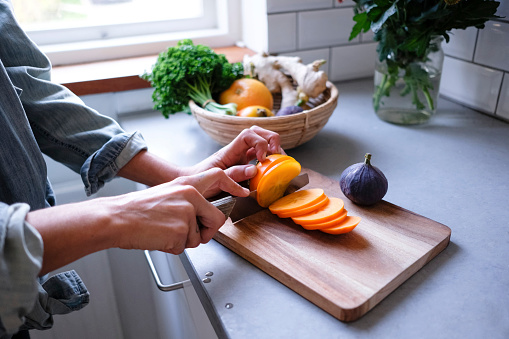 Midsection of woman slicing persimmon on cutting board at kitchen counter - gettyimageskorea