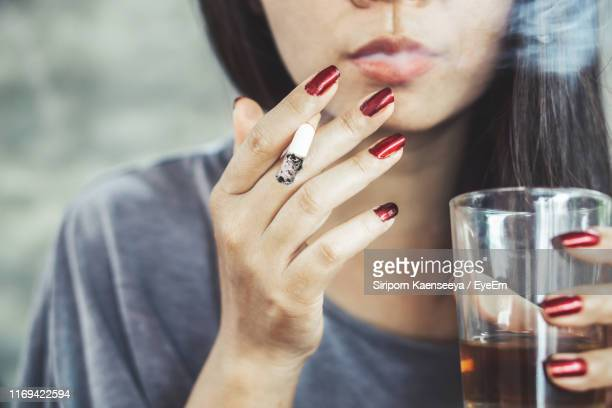 midsection of woman smoking and drinking alcohol - beautiful women smoking cigarettes stock pictures, royalty-free photos & images