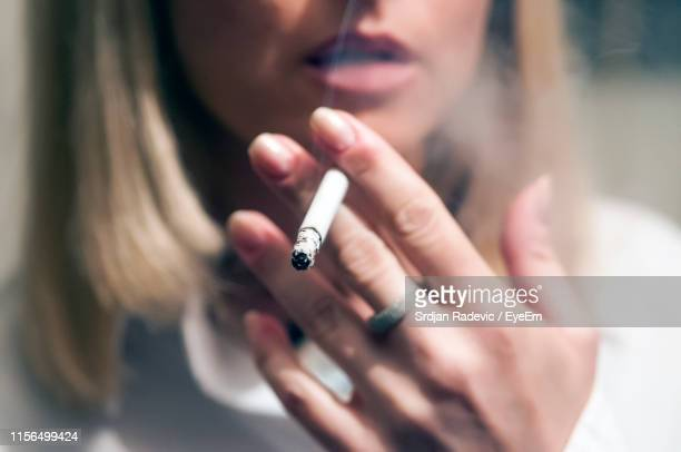 midsection of woman smoking cigarette - femme qui fume photos et images de collection
