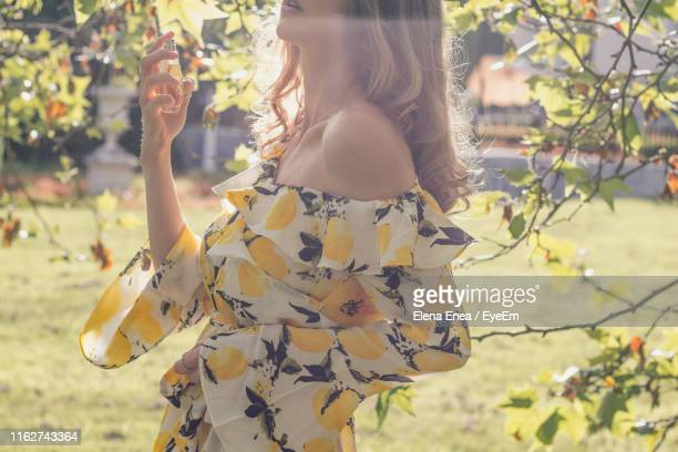 midsection of woman spraying perfume by tree - perfume stock pictures, royalty-free photos & images