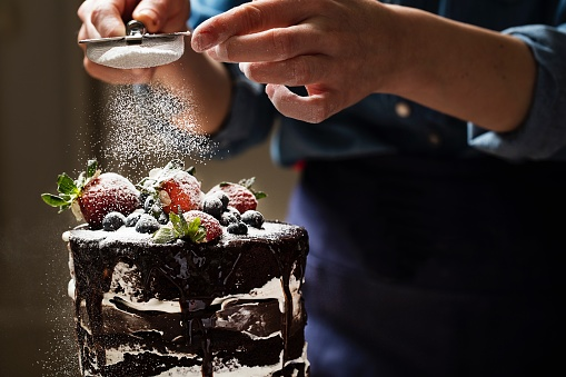 Midsection Of Woman Sprinkling Powdered Sugar On Cake - gettyimageskorea
