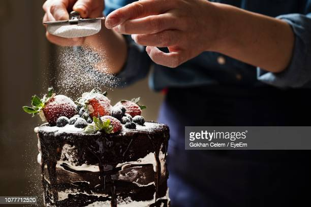 midsection of woman sprinkling powdered sugar on cake - dessert stock pictures, royalty-free photos & images