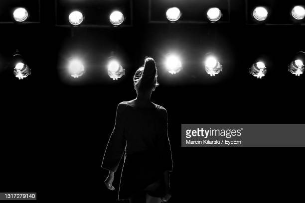 midsection of woman standing by illuminated lights at night - fashion model stock pictures, royalty-free photos & images