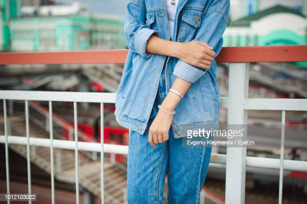 Midsection Of Woman Standing By Railing
