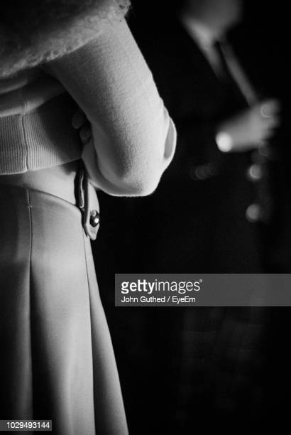 Midsection Of Woman Standing In Darkroom
