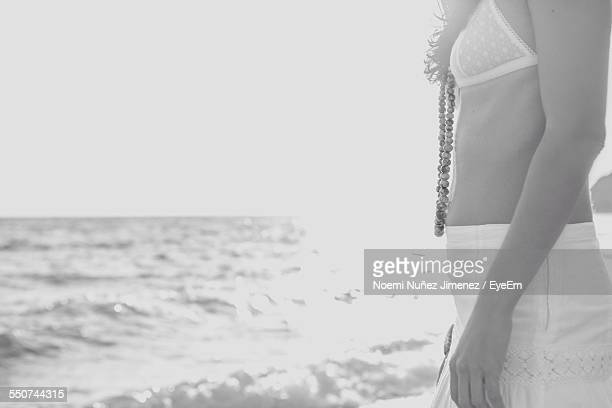 Midsection Of Woman Standing On Beach Against Clear Sky
