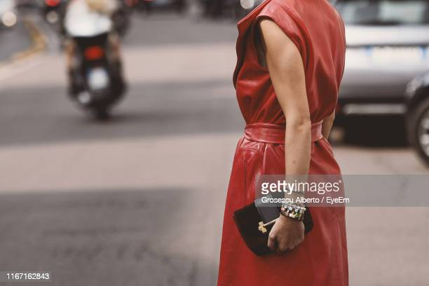 midsection of woman standing on footpath in city - brown purse stock pictures, royalty-free photos & images