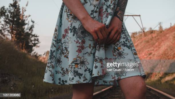 midsection of woman standing on railroad track - floral pattern skirt stock pictures, royalty-free photos & images