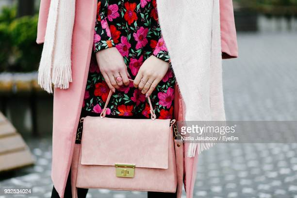 midsection of woman standing on street - pink purse stock pictures, royalty-free photos & images