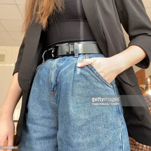midsection of woman standing with hand in pocket - leather belt stock pictures, royalty-free photos & images