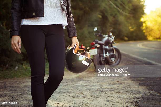 Midsection Of Woman Standing With Helmet By Motorcycle