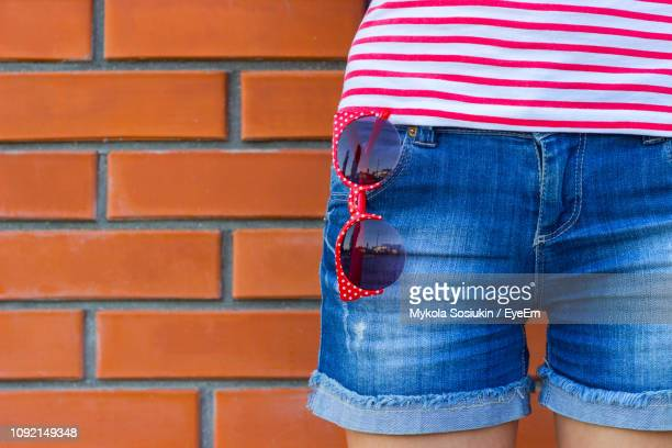 midsection of woman standing with sunglasses in pocket against brick wall - denim shorts stock pictures, royalty-free photos & images