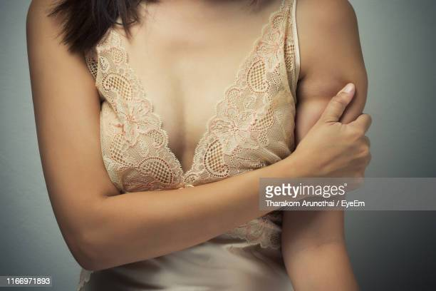 midsection of woman suffering from arm pain against gray background - nachthemd stockfoto's en -beelden