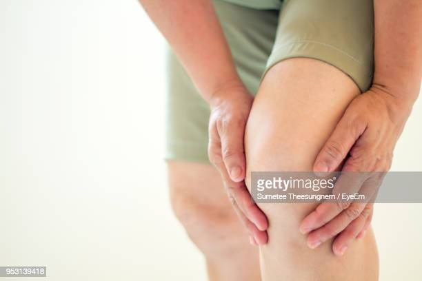 midsection of woman suffering from knee pain - knee stock photos and pictures