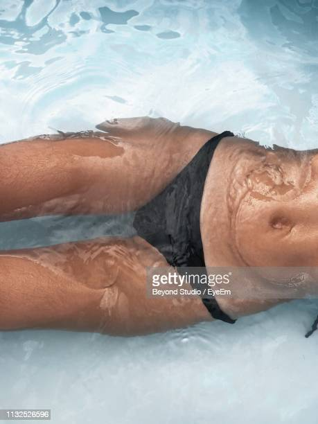 midsection of woman swimming in pool - wet knickers stock pictures, royalty-free photos & images
