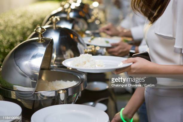 Midsection Of Woman Taking Food In Plate