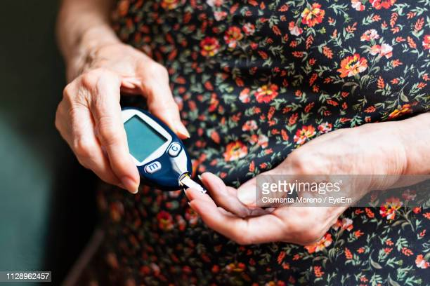 midsection of woman testing blood sugar - diabetes stock pictures, royalty-free photos & images