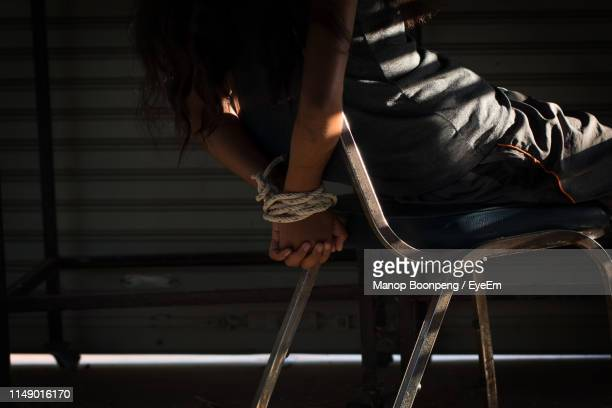 midsection of woman tied up with rope on chair in room - female torture stock-fotos und bilder