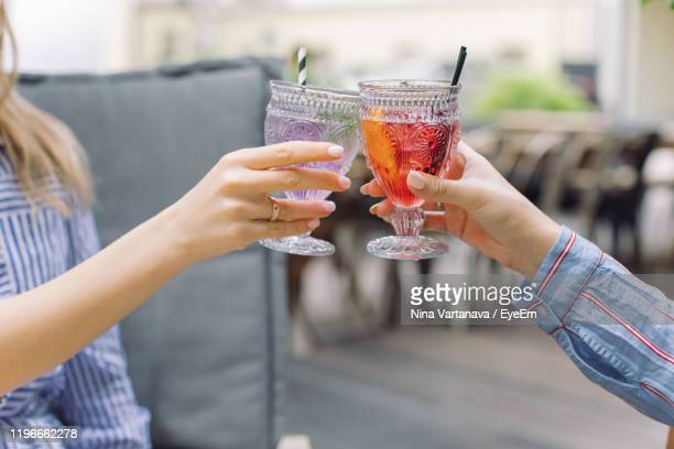 midsection of woman toasting with female friend in cafe - celebratory toast stock pictures, royalty-free photos & images