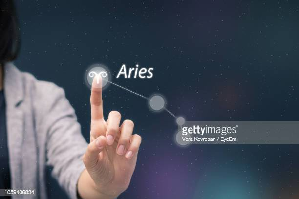 Midsection Of Woman Touching Astrology Sign On Digital Display