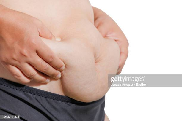 midsection of woman touching belly against white background - human abdomen stock pictures, royalty-free photos & images