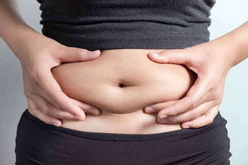 Midsection Of Woman Touching Stomach Against Gray Background - gettyimageskorea