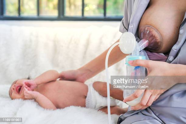 midsection of woman using breast pump while sitting by baby boy at home - breast pump stock pictures, royalty-free photos & images